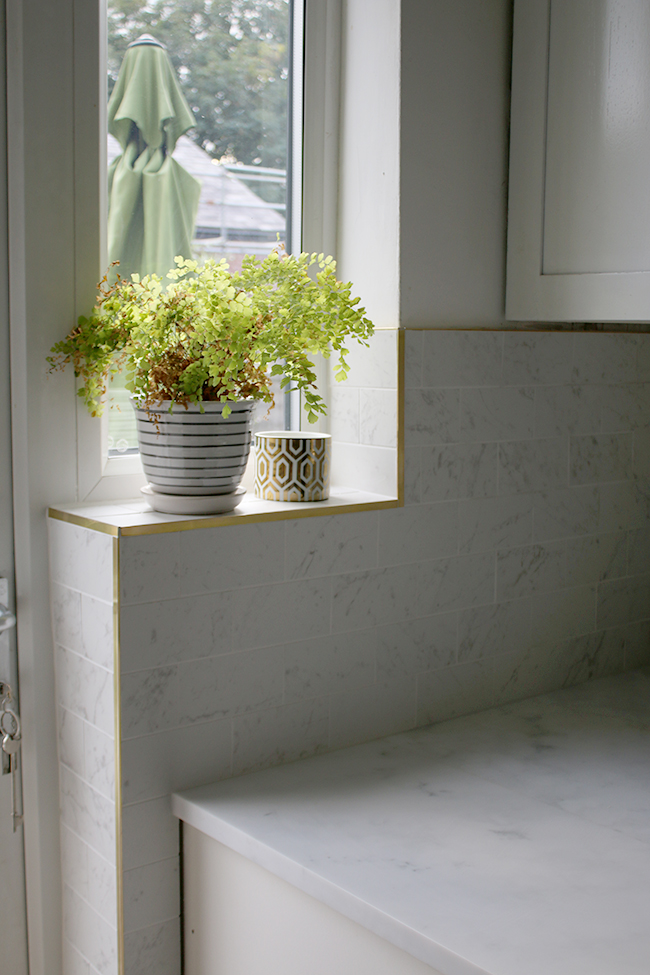 Marble effect porcelain tiles with brass trim work along windowsill in the kitchen