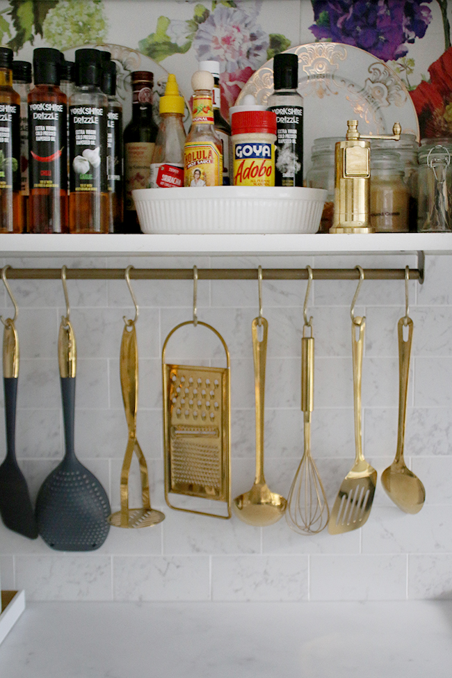 Marble effect kitchen tiles with gold hanging utensils and open storage in the kitchen