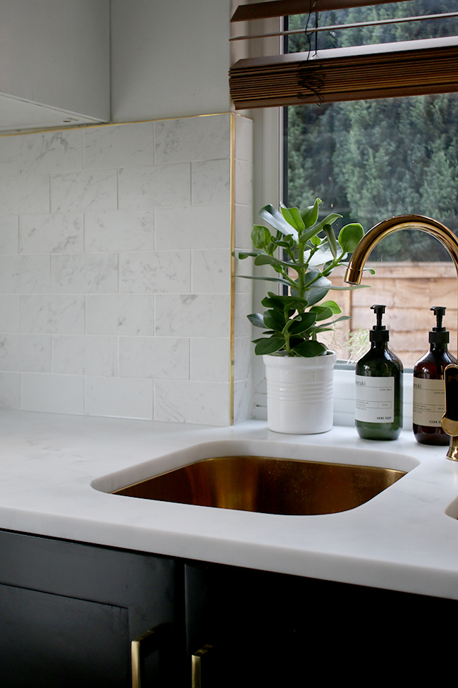 gold sink and tap with white marble tiles and brass trim