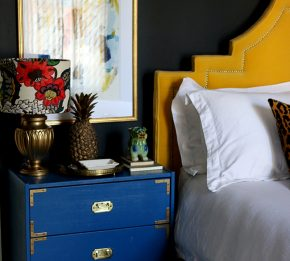 black bedroom with blue nightstand and yellow headboard