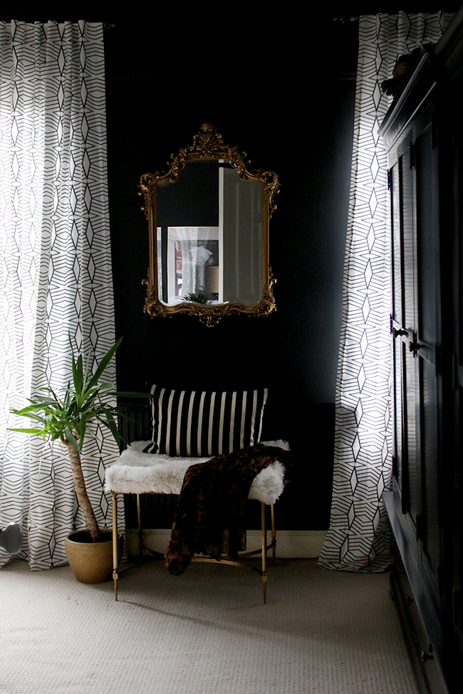 black walls with ornate mirror and brass bench with patterned curtains