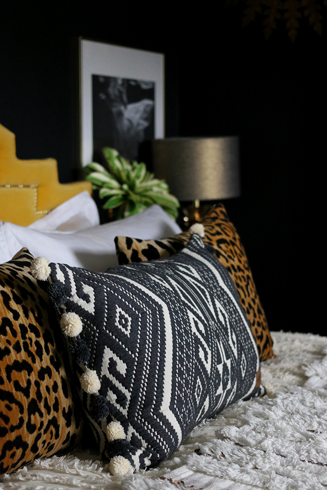 Boho glam bedroom with leopard print cushions and Moroccan wedding blanket