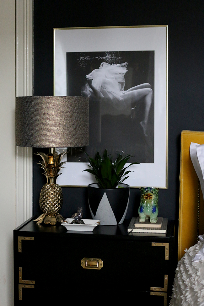 black campaign style nightstand with gold pineapple lamp