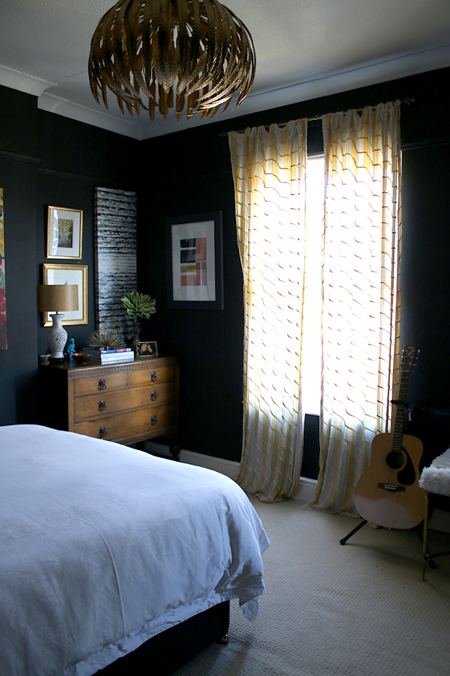 black bedroom with yellow curtains