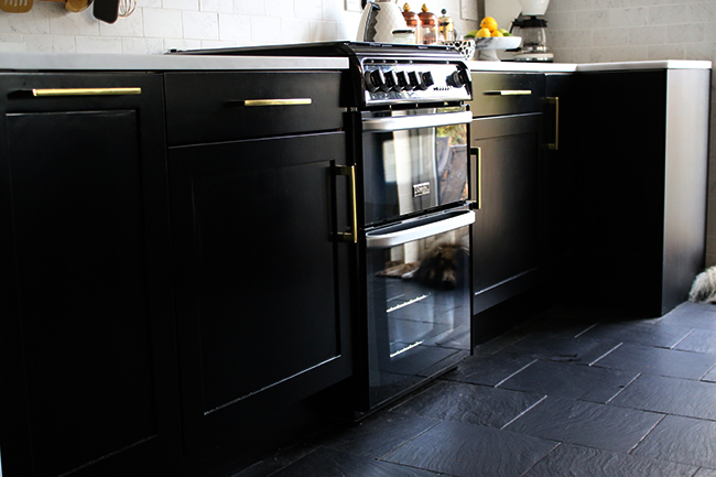 black kitchen cabinets with gold hardware and slate flooring