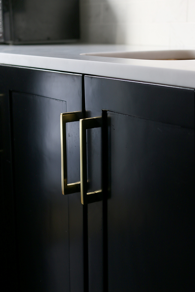 black kitchen cabinets with gold pull handles