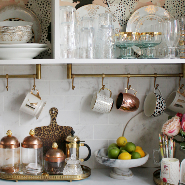 kitchen with brass rails and open storage in white and gold
