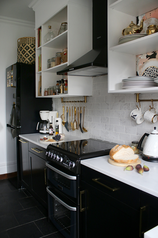 Kitchen with black appliances and cupboards with white open shelving, marble tiles and brass accents