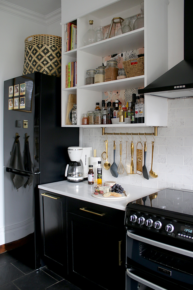 kitchen with black cupboards with white open shelving, marble tiles and brass accents