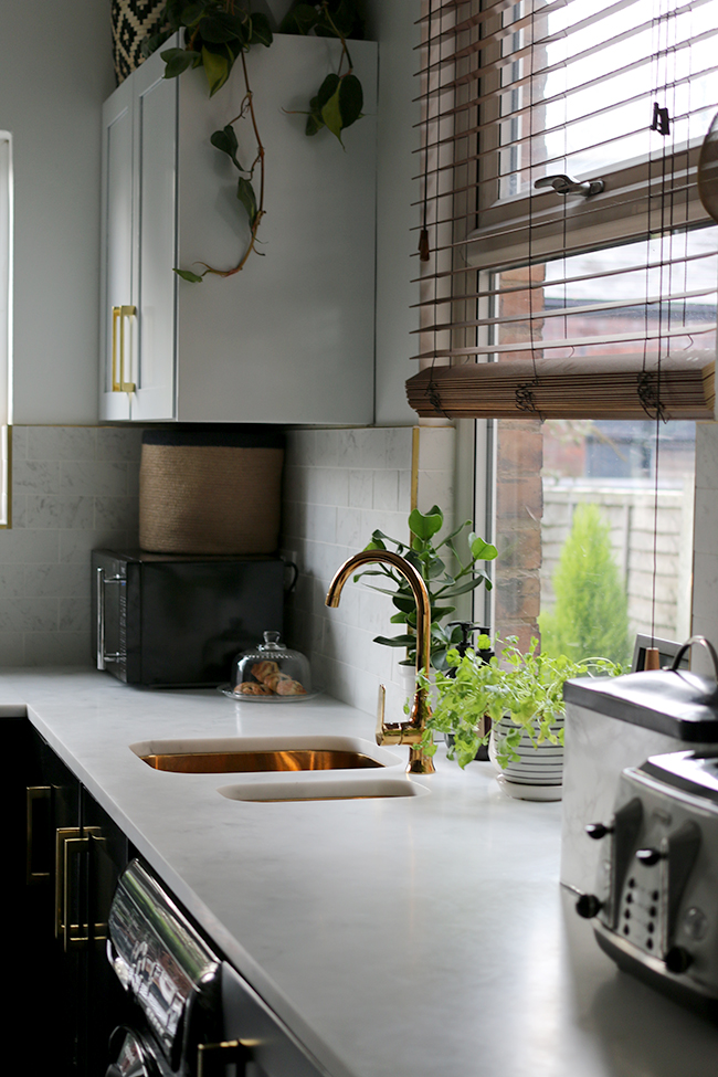 kitchen with black cupboards with white open shelving, marble tiles, gold sink and gold tap