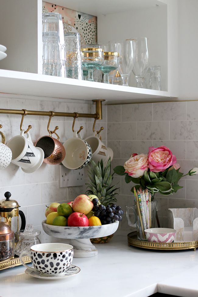 kitchen corner with marble tiles, brass rail with cups and fruit bowl