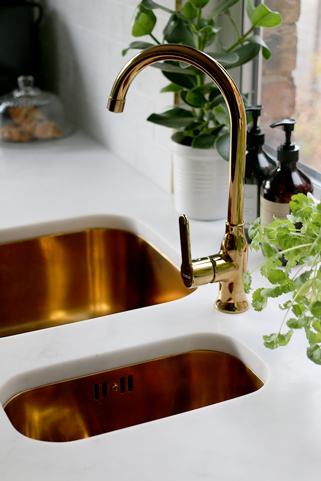 gold sink and faucet with marble effect worktop