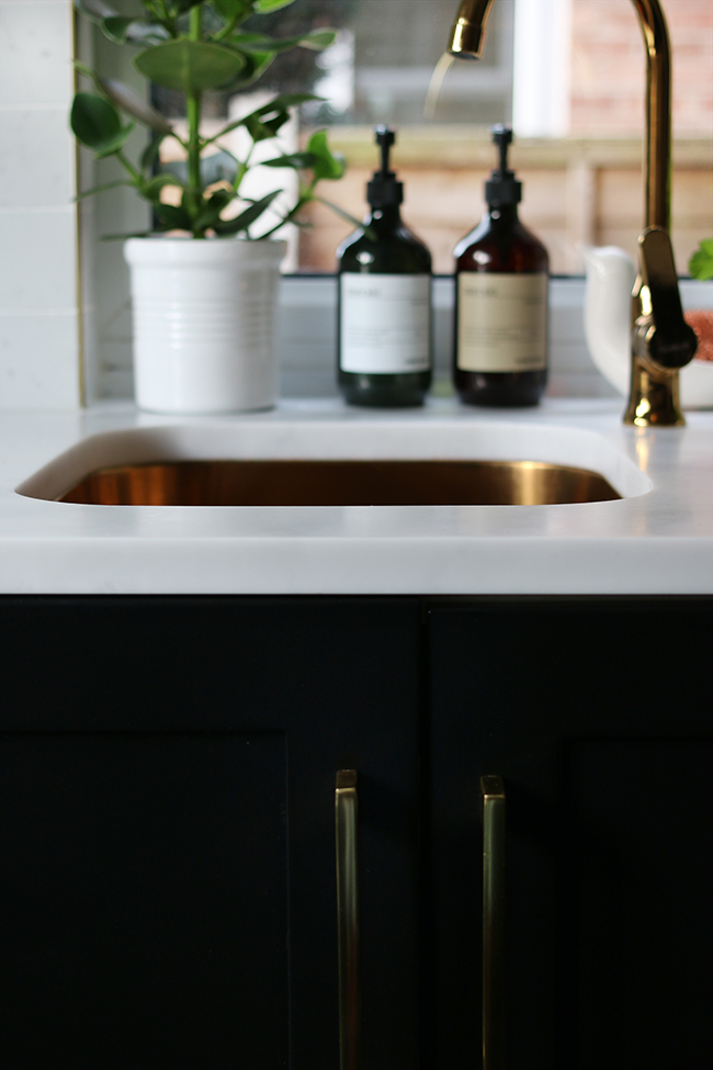 black lowers with marble effect countertop and gold sink and faucet