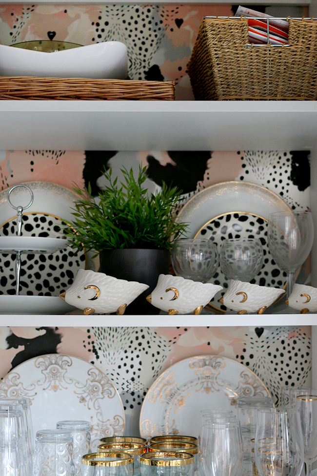 open shelf styling with peach and spotty wallpaper and gold accents