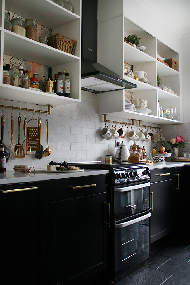 black white and gold kitchen with slate floors, black lowers and white open shelving with brass details