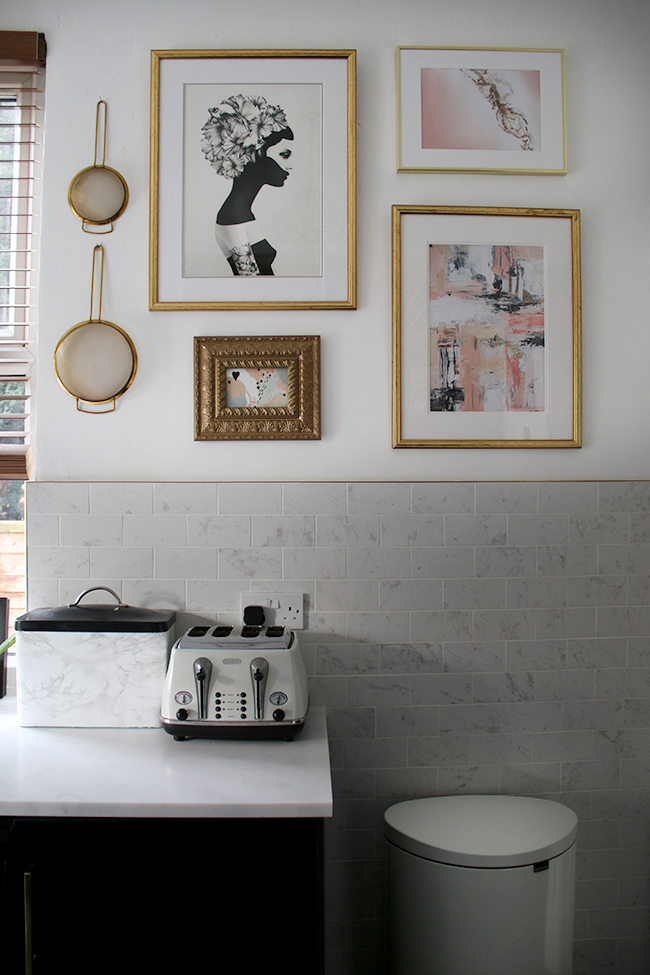 pink grey and gold gallery wall in kitchen with white marble effect tiles