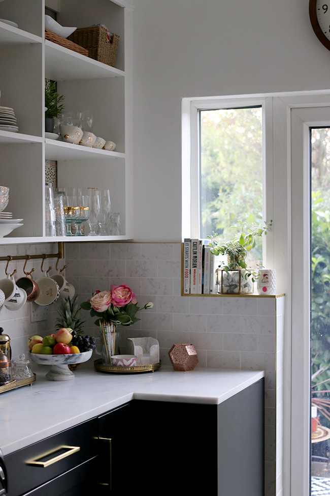 kitchen with brass tile trim and marble effect tiles
