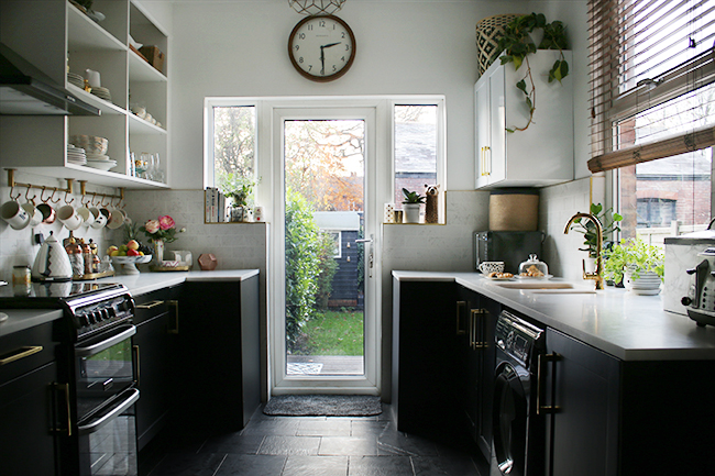 black white and gold kitchen with slate floors, black lowers and white open shelving with brass details and gold faucet