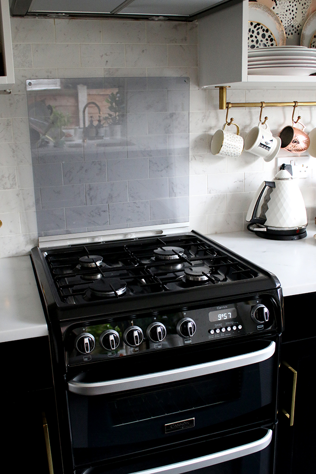 black oven with flip up splashback screen with black cupboards and gold hardware in kitchen