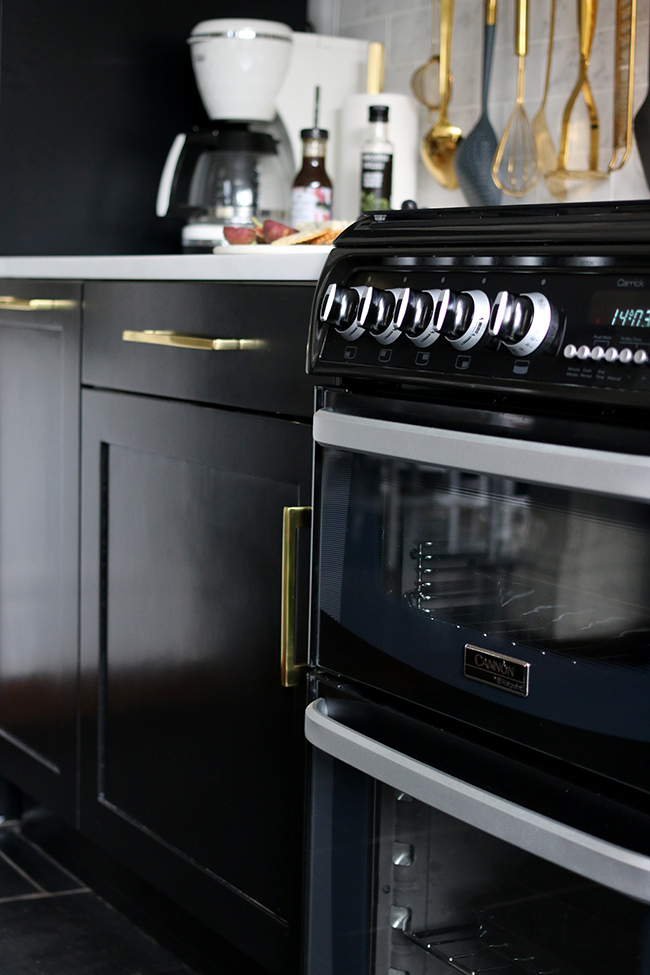 black oven with black cupboards and gold hardware in kitchen