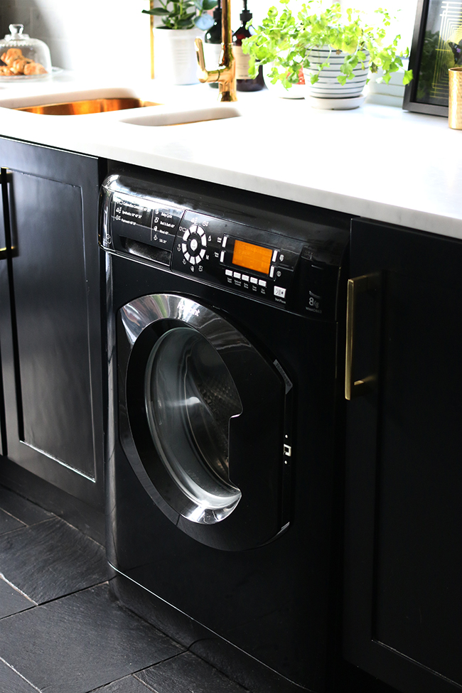 Hotpoint 8k black washing machine from ao.com in black kitchen with gold hardware