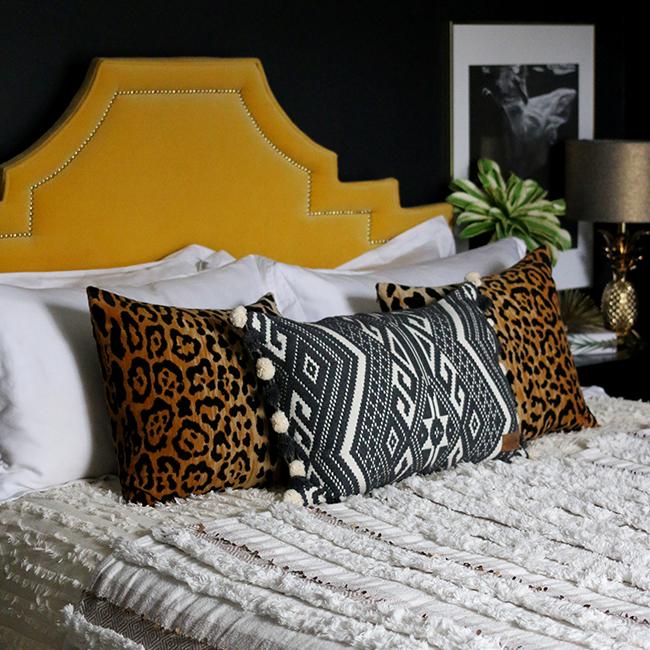 black bedroom with leopard print cushion, yellow headboard and moroccan wedding blanket throw