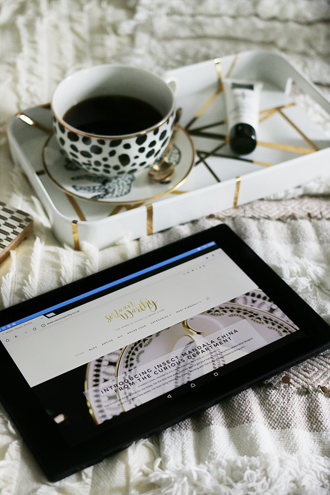 flatlay with tablet on bed with cup of coffee and leopard print neutrals texture