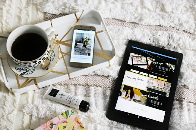flatlay with tablet and mobile on bed with cup of coffee and leopard print neutrals texture