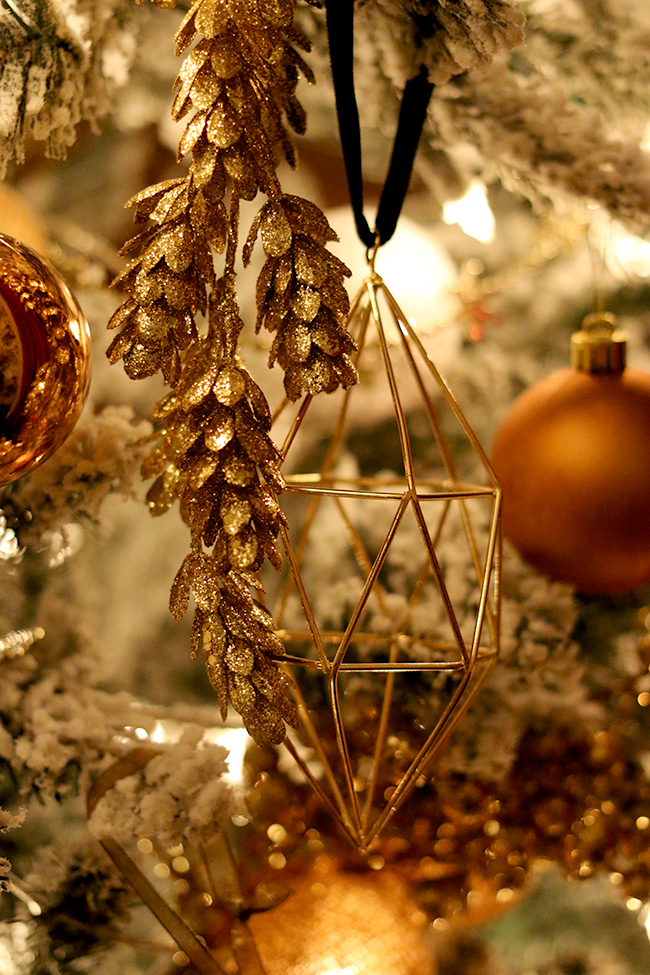 geometric gold christmas ornament on tree at night