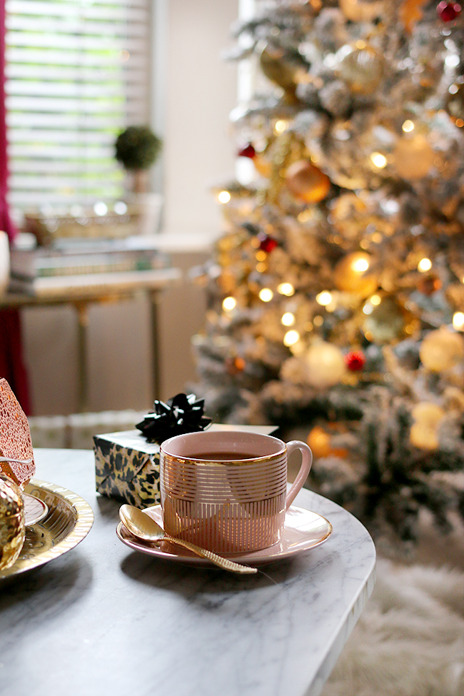 Pink and gold mug tea cup with christmas tree in background bokeh