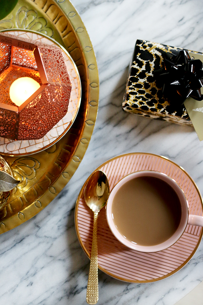pink cup with coffee shot from above with christmas present and copper candle