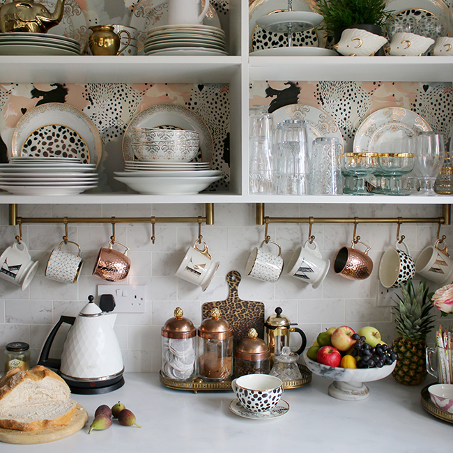 kitchen open shelves with wallpaper copper and gold accents and white marble tiles