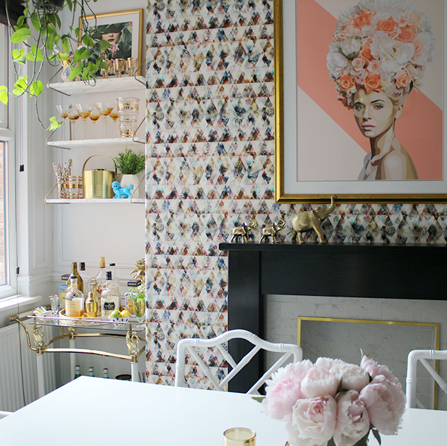 dining room with graphic wallpaper and shelving bar cart in pink gold and black