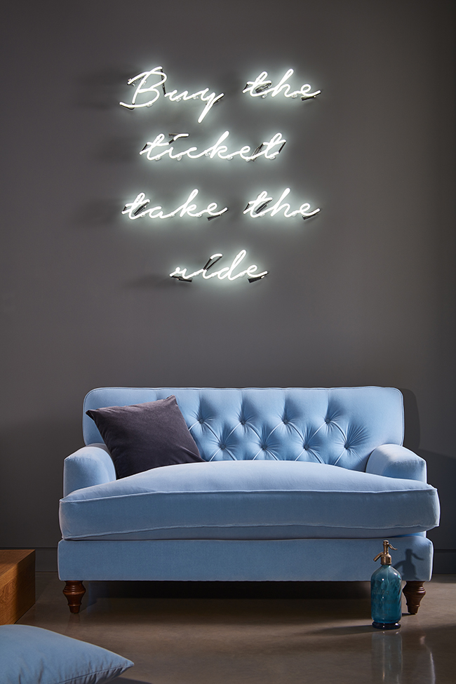 light blue velvet button back love seat with neon sign above from darlings of chelsea