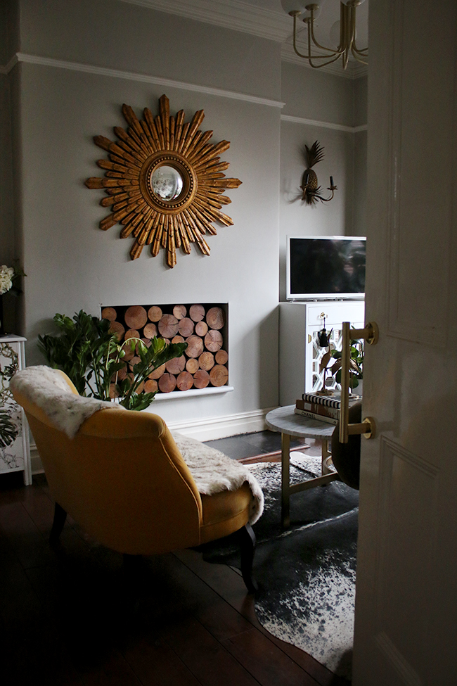pale grey living room with large gold starburst mirror decorative wood in fireplace and cowhide rug with yellow velvet loveseat