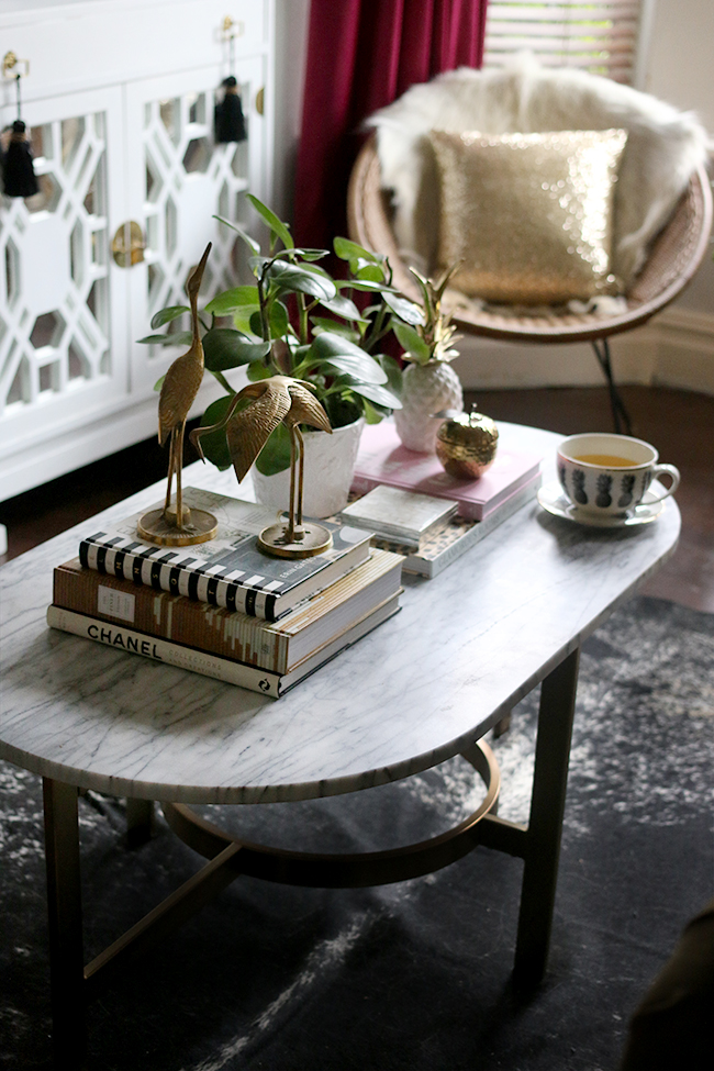 marble and gold coffee table on black speckled cowhide rug with vintage brass - coffee table styling