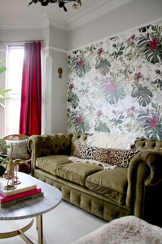 eclectic boho glam living room with olive green chesterfield sofa and tropical wallpaper