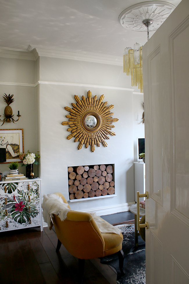 eclectic glam living room with dark flooring and gold starburst mirror