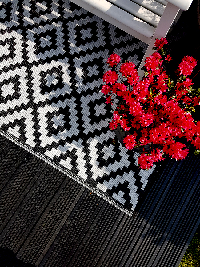 black decking with black and white outdoor rug and pink azaleas