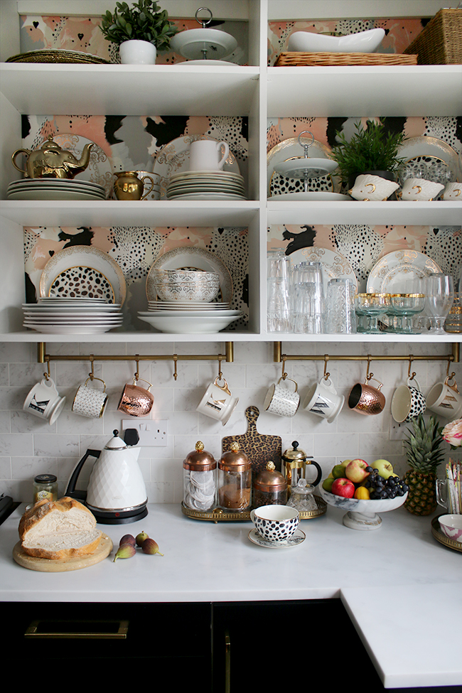 open shelving in kitchen with wallpaper and gold and copper accents