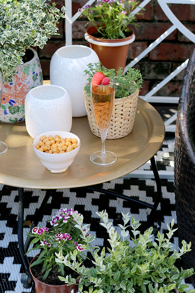 gold table with black and white outdoor rug and white candle lanterns from West Elm