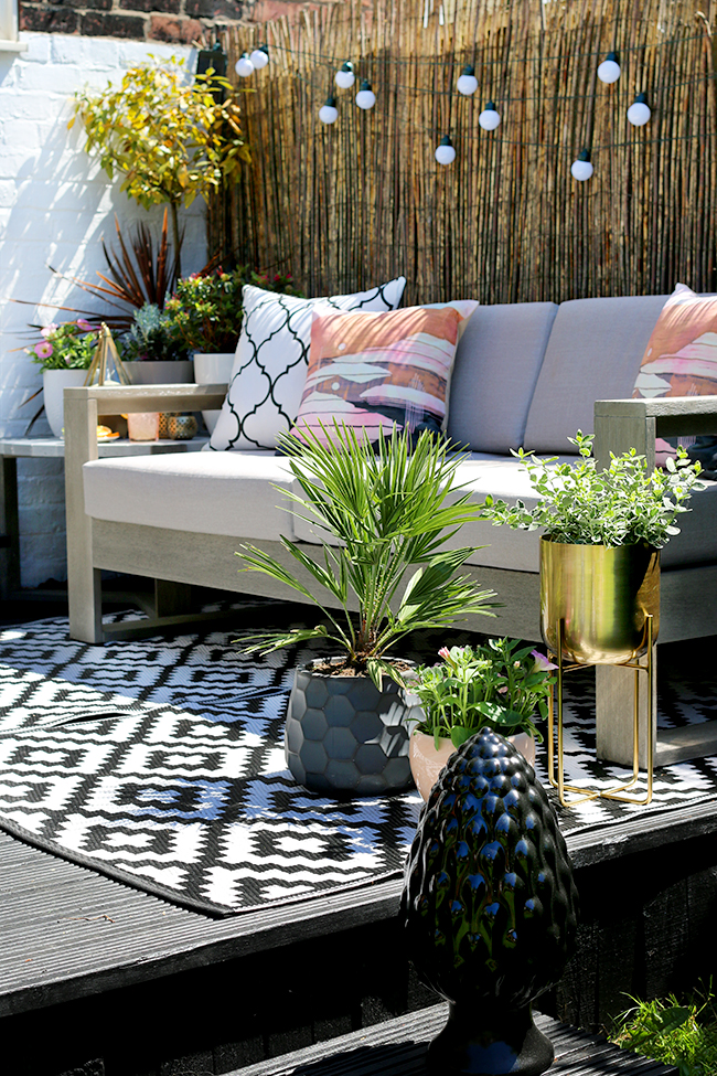 outdoor garden design patio with grey sofa