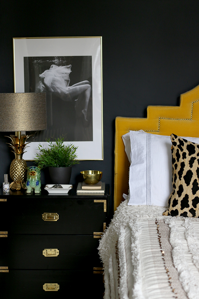 black bedroom with black and white photography art, black campaign style ikea nightstand and yellow headboard