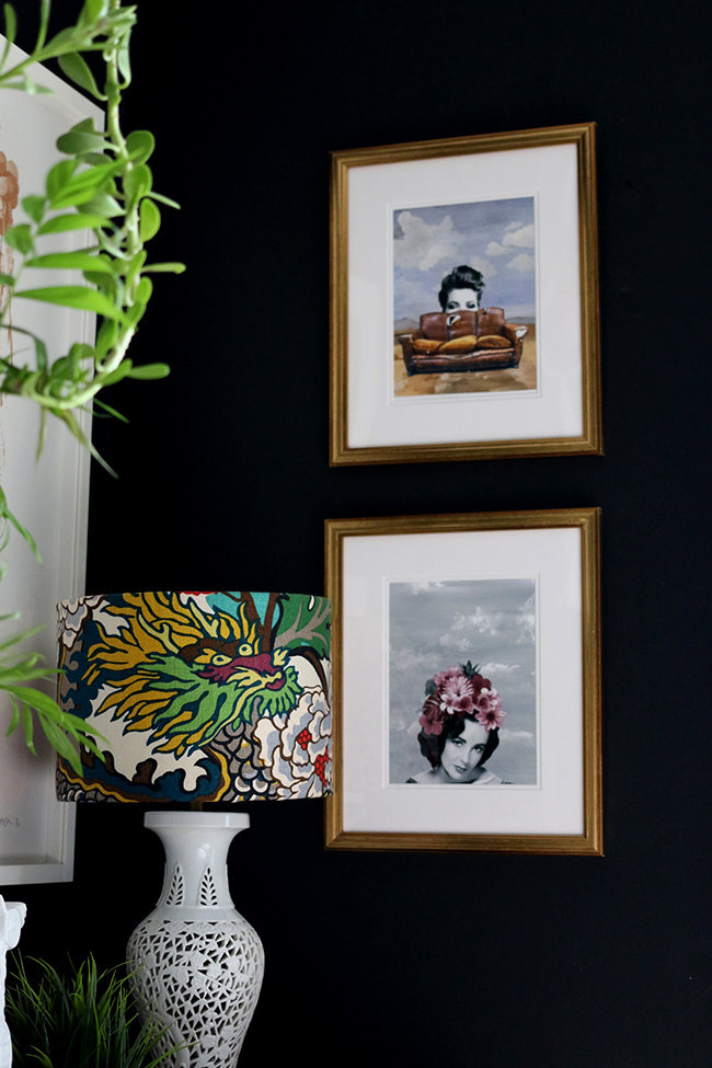 black wall with art prints and plants
