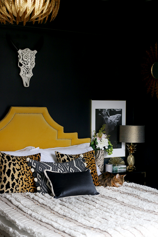 black bedroom with yellow velvet headboard leopard print cushions and gold pineapple lamp