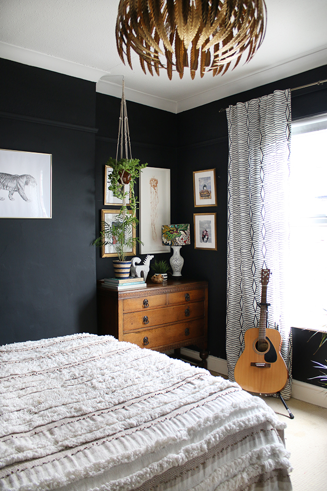 black boho glam bedroom with vintage dresser and plants