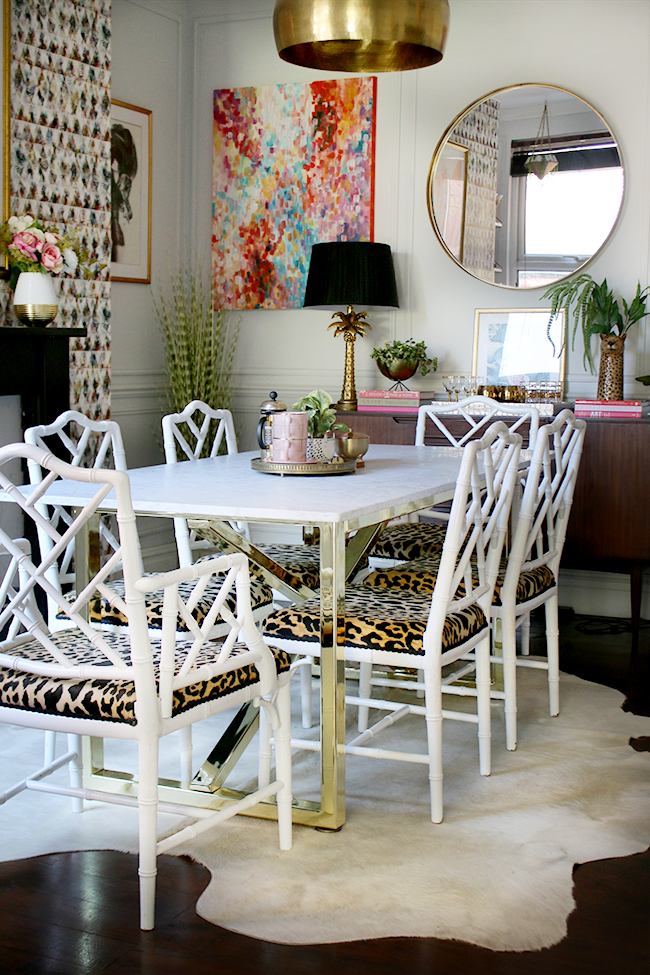 dining room with marble table and brass base with faux bamboo chairs