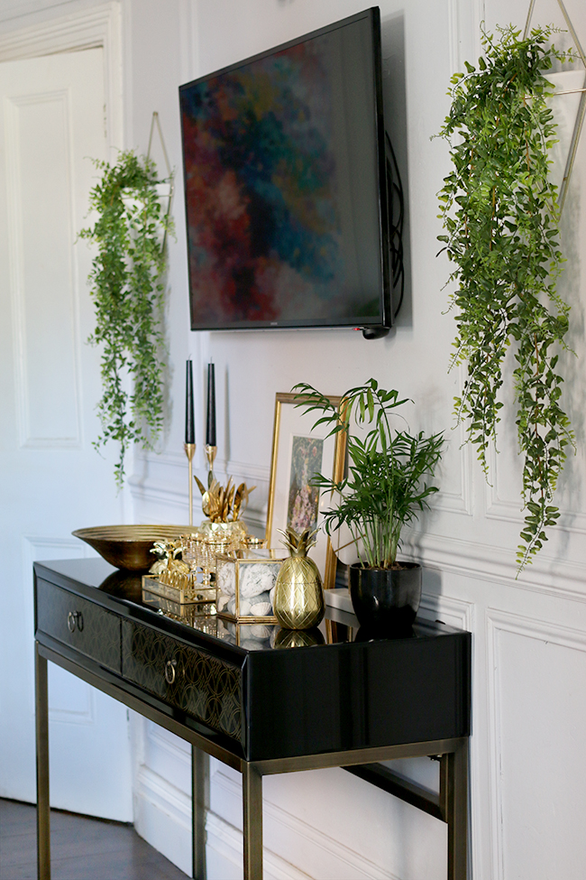 faux ivy in wall planters with wall mounted tv and black and gold sideboard