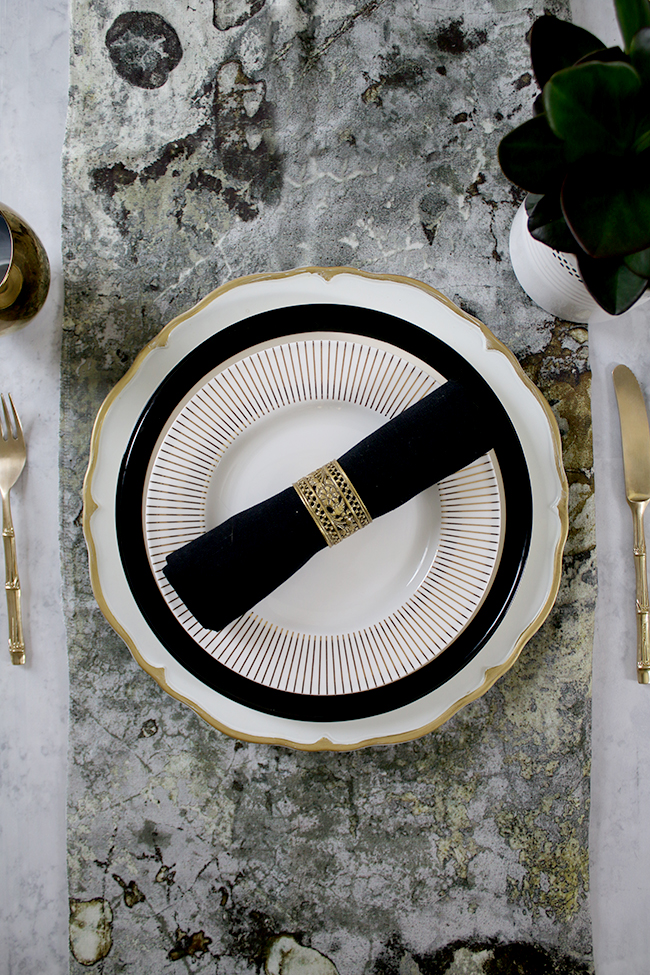 table setting mix and match in black white and gold with a touch of green