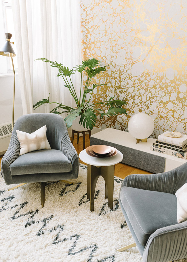 Gold wallpaper with luxe finishes grey velvet chairs